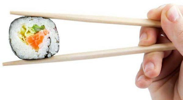 photo of sushi in chop sticks